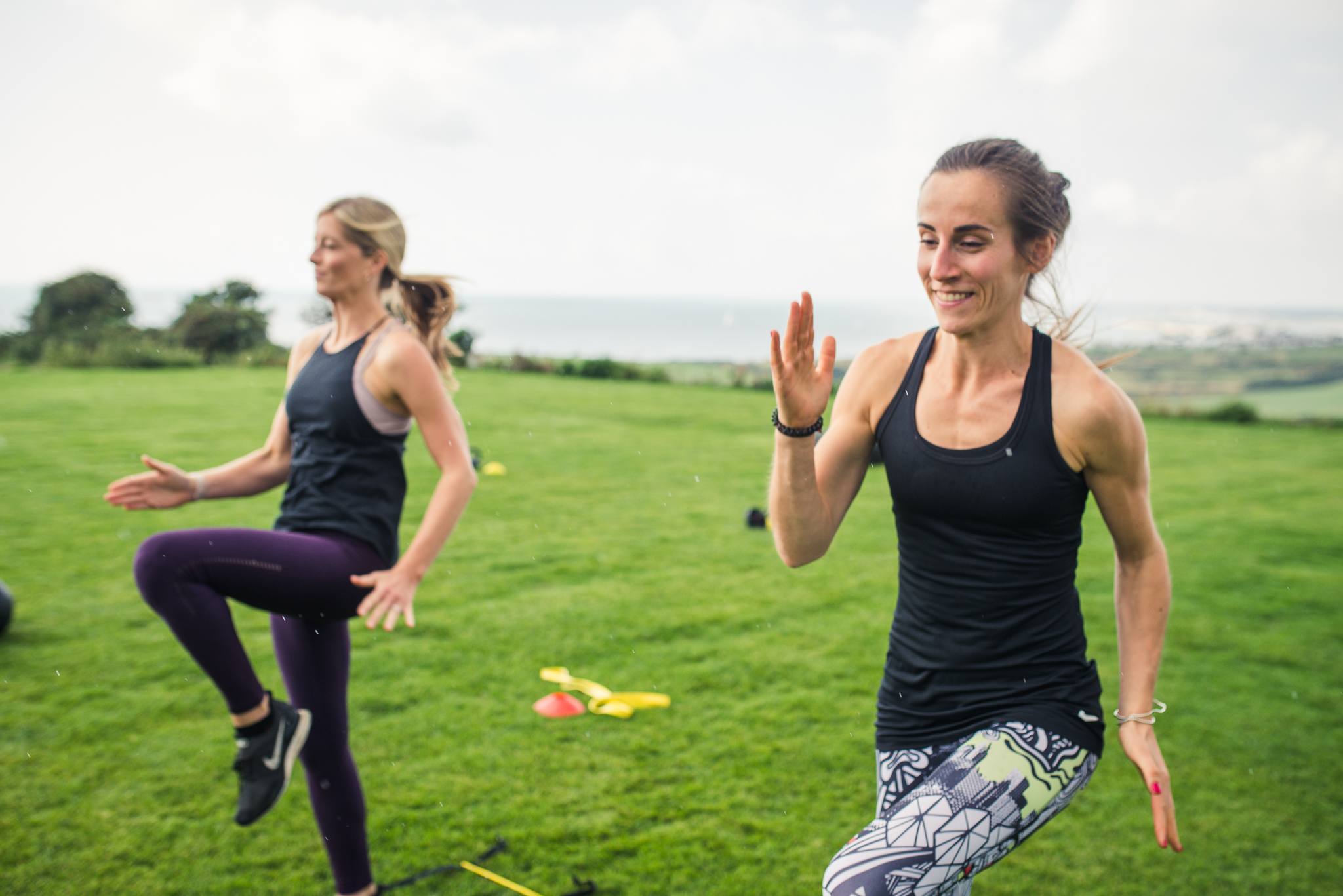 Two women doing a fitness class outdoors on the Isle of Wight