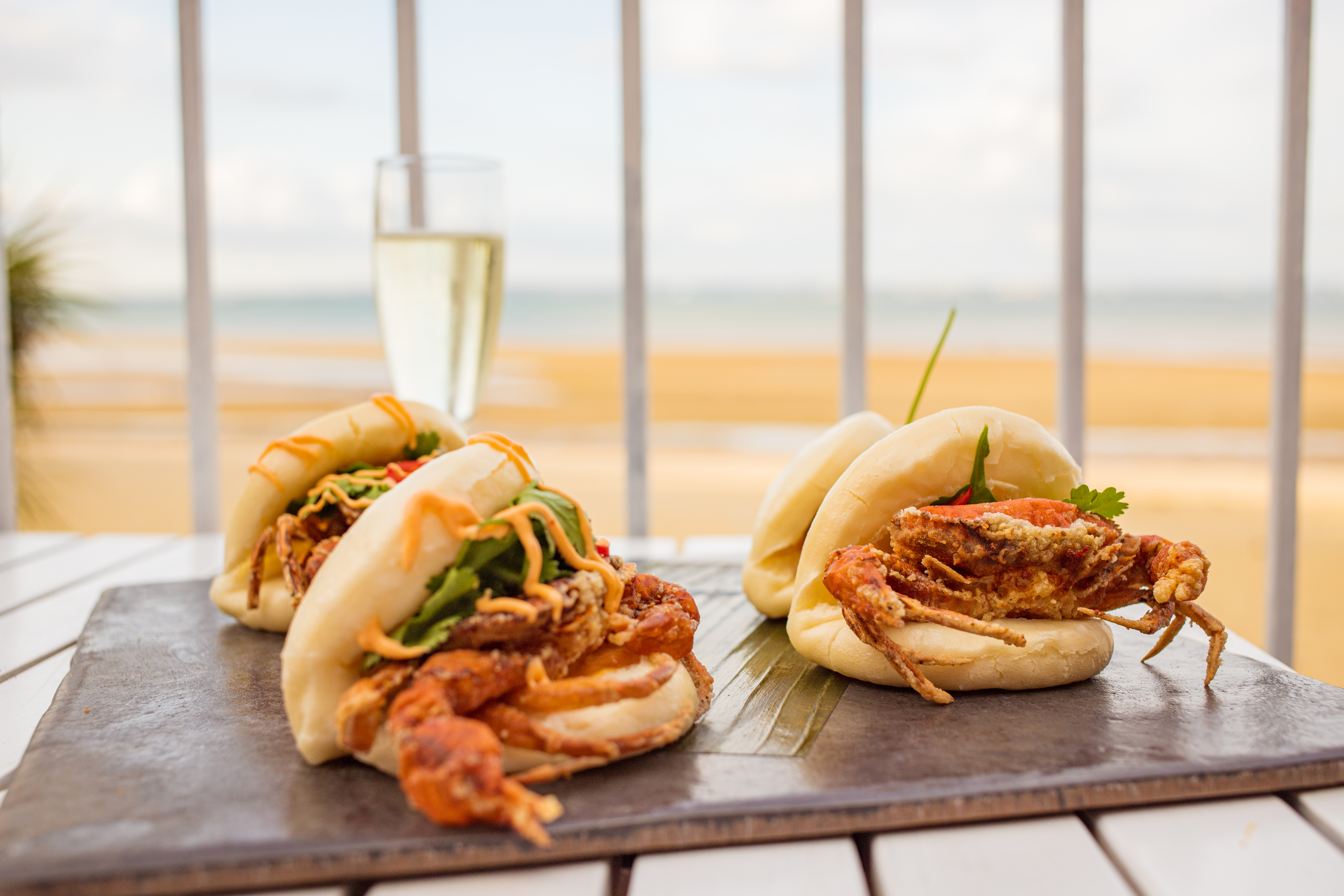 A slate of Bao buns and a glass of bubbly on a table overlooking the beach at Cadet Beach Club, Ryde, Isle of Wight