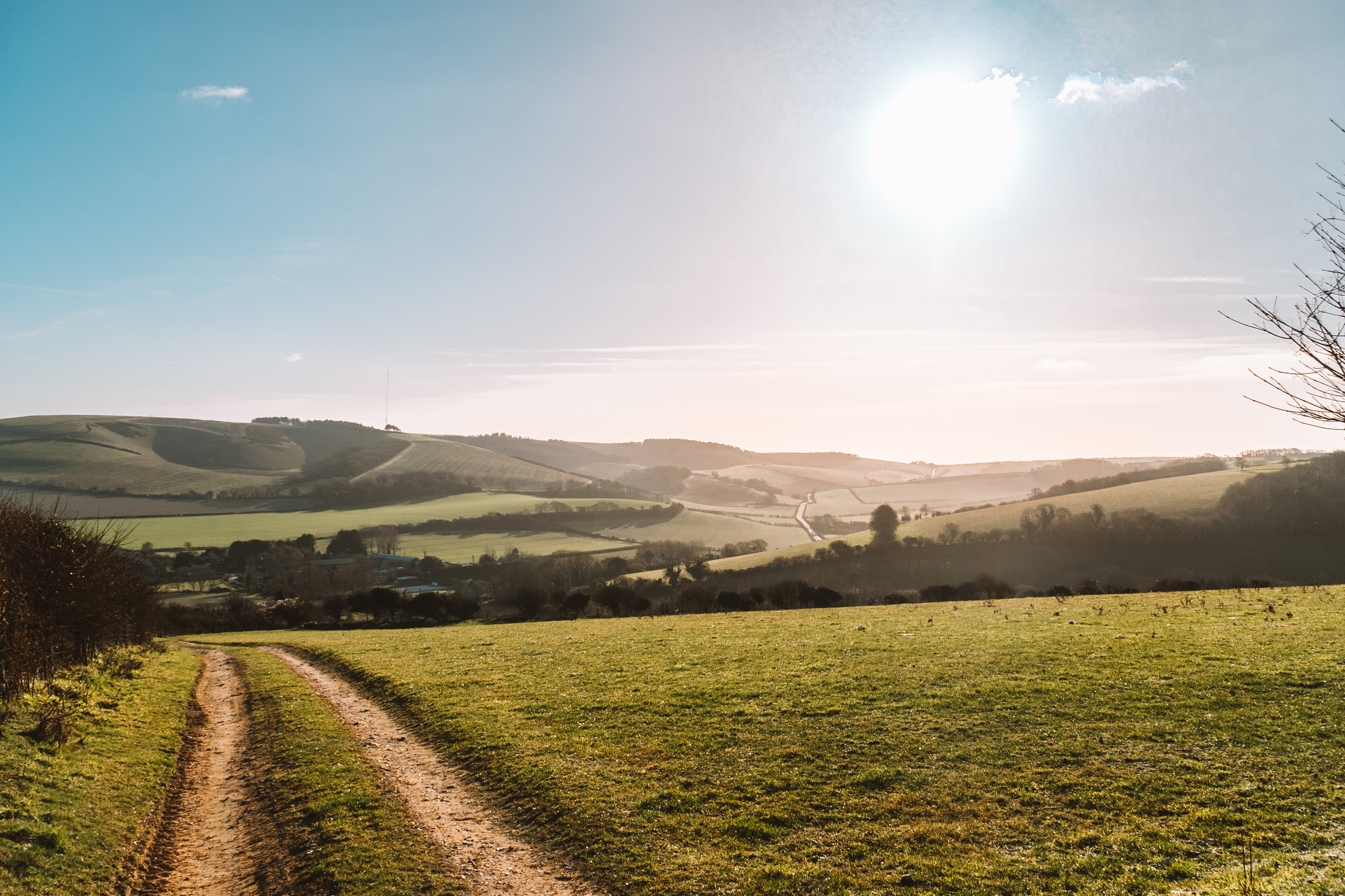 The sun shines over a countryside scene of rolling hills and fields on the Isle of Wight