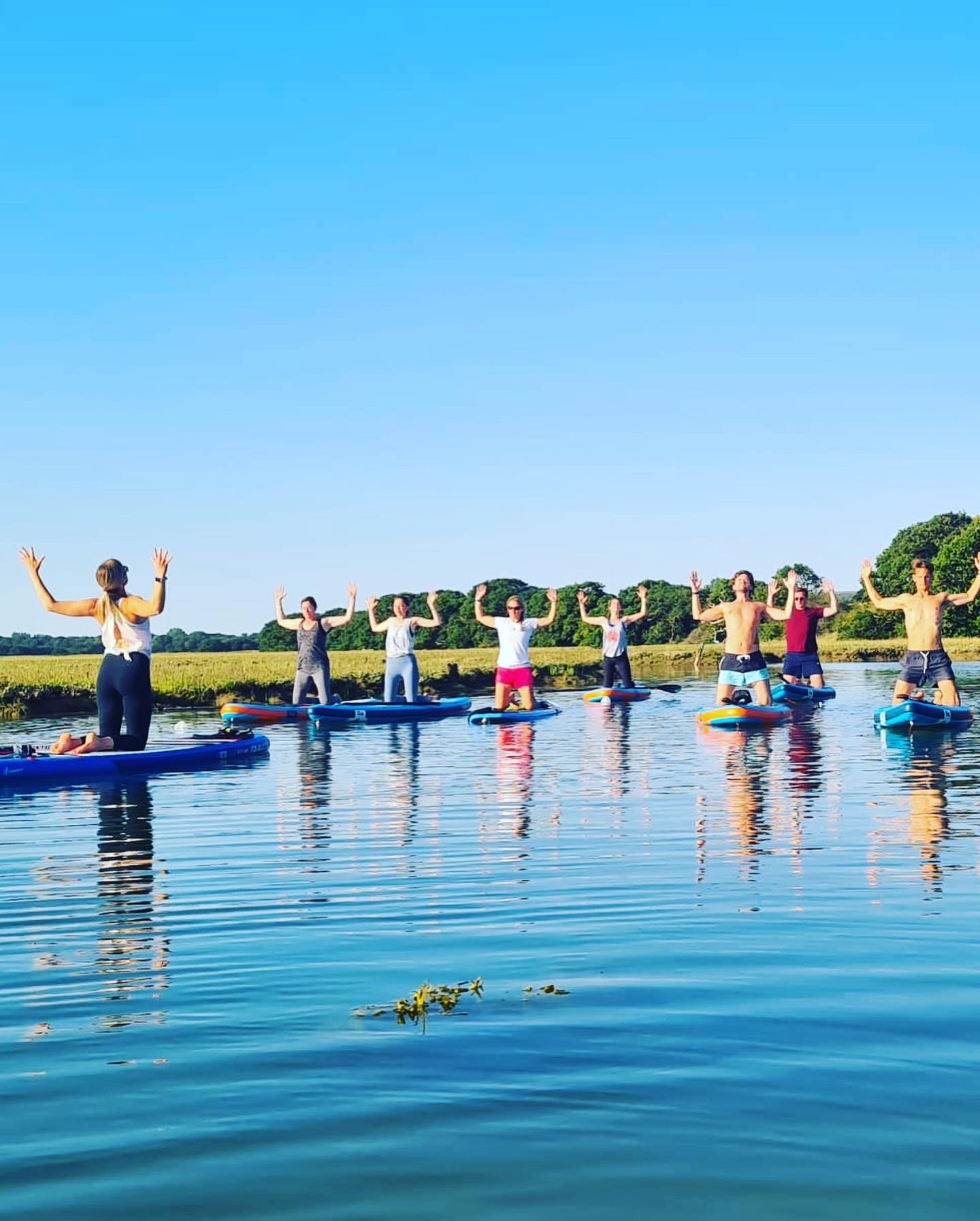 A group of people posing while doing stand up paddleboard yoga on the River Yar, Isle of Wight
