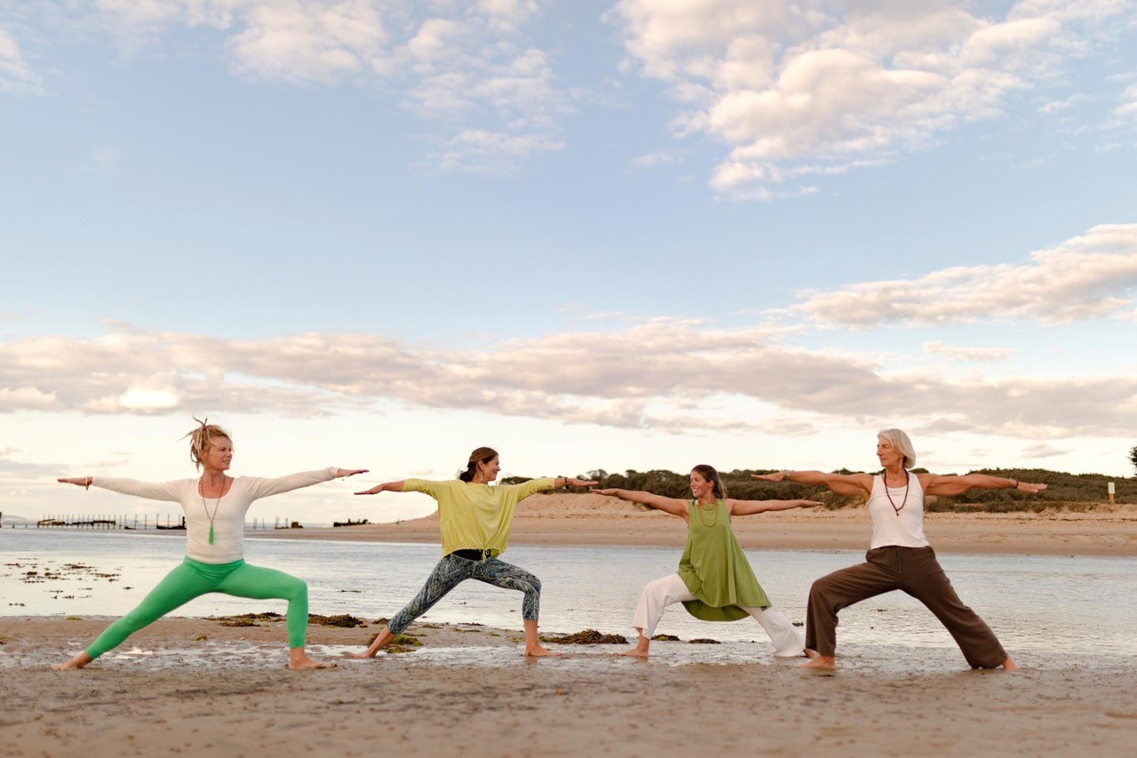 A group of women in various yoga poses on a sandy beach on the Isle of Wight