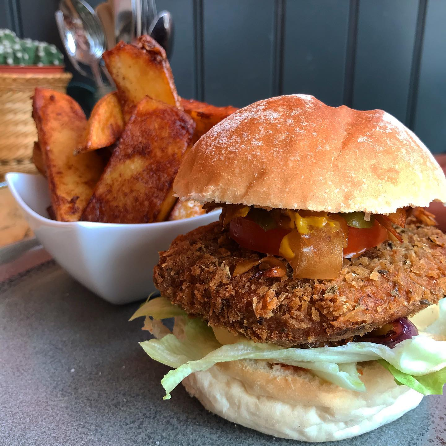 Vegan burger in a bun and bowl of chips from Peach, Isle of Wight