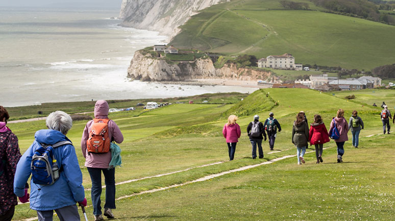 A group of walkers walking between Yarmouth and Brighstone on the Isle of Wight with the coastline in the background